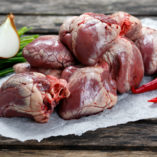 Raw Lamb Hearts on crumpled paper, decorated with vegetables. on
